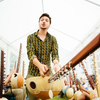 A teacher holding a kora during a workshop at WOMAD