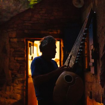 Adam Doughty playing kora, standing outside, backlit