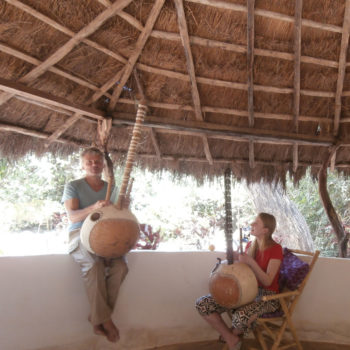 Adam sitting on the wall of the bantamba teaching a seated student
