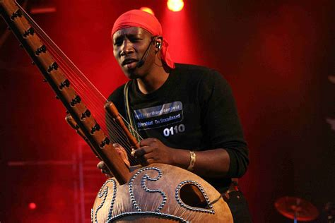 nfaly kouyate standing playing kora