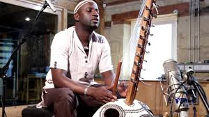 Seckou Keita seated playing kora