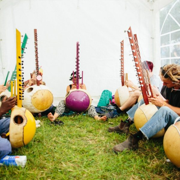 A group of people with some colourful koras at a workshop at WOMAD