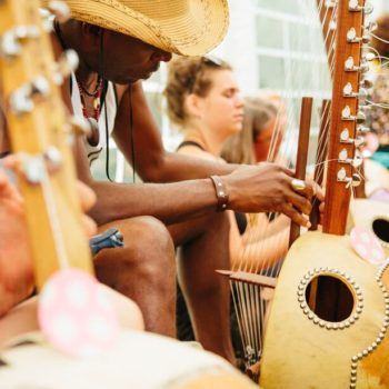 Man looking intently at a kora during a workshop at WOMAD