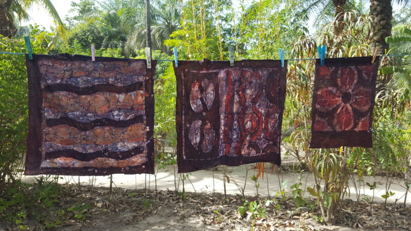 Three batiked squares of cloth drying on a washing line